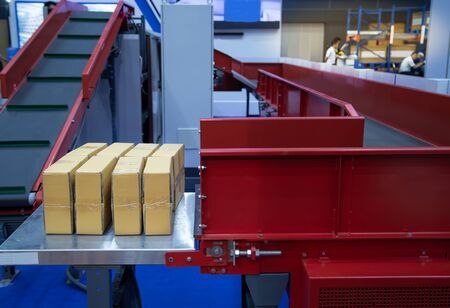 Distribution of cardboard parcel on conveyor belt in warehouse