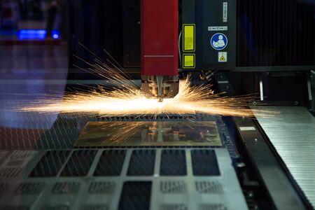 CNC fiber laser cutting machine cutting metal sheet with flying sparks