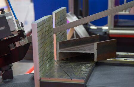 Band saw machine cutting metal I-Beam in workshop