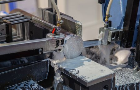 Band saw machine cutting metal rod and cooling with coolant Stockfoto