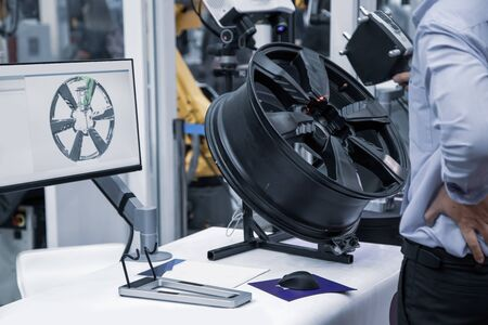 Industry worker use handheld 3D scanner inspecting a wheel