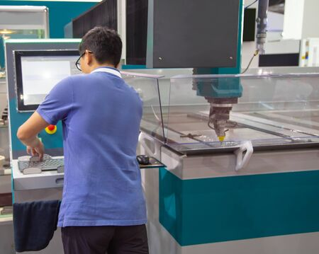 Industrial worker operate abrasive water jet cutting machine Stockfoto