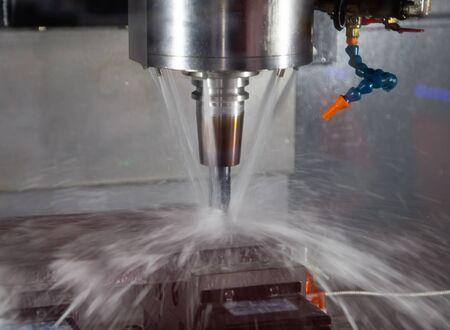 CNC milling machine cutting workpiece with coolant