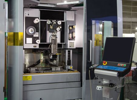 Electrical discharge machine EDM cutting workpiece in workshop