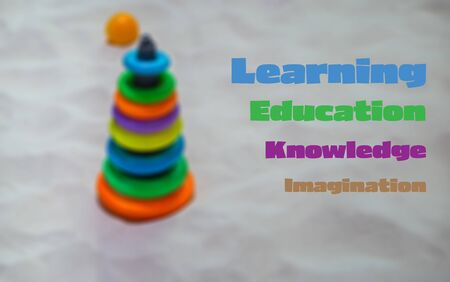 Education learning words on blurred background of plastic cone toy on the beach