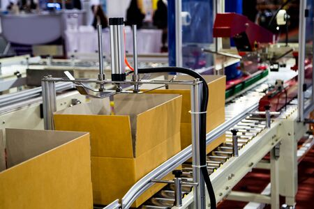Automatic cardboard box packing and tape sealing machine