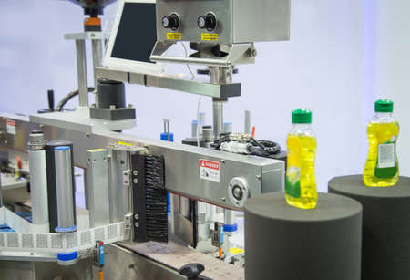 Sample products on bottle labeling machine in industrial machinery
