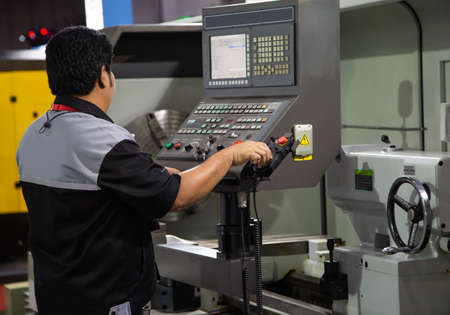 Industrial technician operating CNC lathing machine. Metalworking manufacturing factory Stock fotó