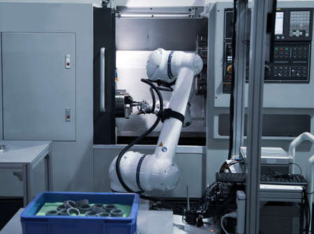 Automated process industrial robot loading metal part to CNC machine. Industrial manufacturing