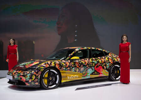 Bangkok, Thailand - April 4, 2021: Presenters with  EV car Porsche Taycan Turbo S decorated with elephant art designed by NARAYA exhibited in BANGKOK INTERNATIONAL MOTOR SHOW 2021