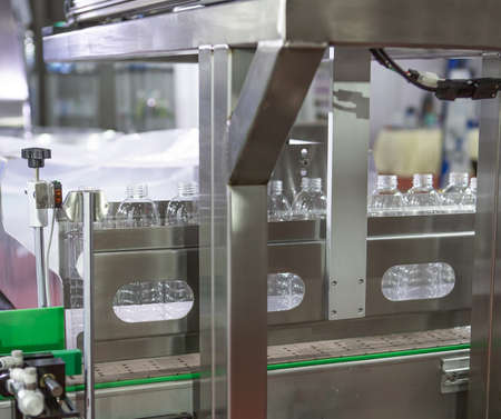 Production line collecting empty plastic bottle from blowing machine before packing in plastic bag