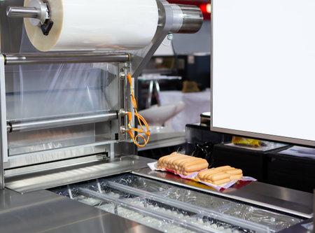 Package of sausage on food vacuum packaging sealing machine in food industrial factory