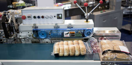 Automatic packing of bakery product flow pillow packing machine. Bread, toast, bun plastic wrapping machine on bakery production line