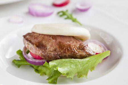 Gua bao, steamed sandwich, grilled pork bun with vegetables, presa iberica. Foto de archivo