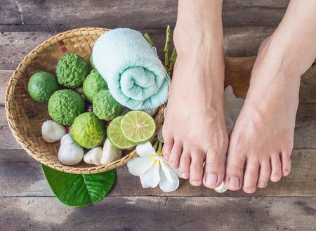 beautiful feet: beautiful female feet with Kaffir Lime on wooden background