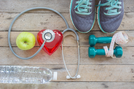 water aerobics: Healthy concept , diet plan with sport shoes and bottle of water and Dumbell on wooden background