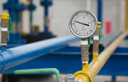 outside machines: manometer, measuring gas pressure. Pipes and valves on the background. Selective focus.