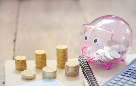 The concept of saving money for business, deposit coin in piggy bank, calculators and coins placed on a wooden background with blank for text