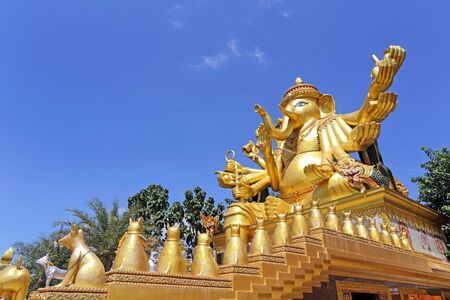 Golden ganecha statue sitting with blue sky background at Mae Ya Som Temple in Sa Kaeo Province of Thailand