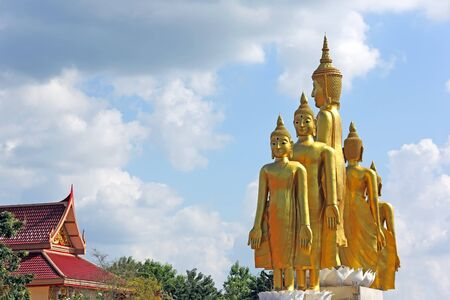 5 golden Buddha statue standing with blue sky background at Mae Ya Som Temple in Sa Kaeo Province of Thailand