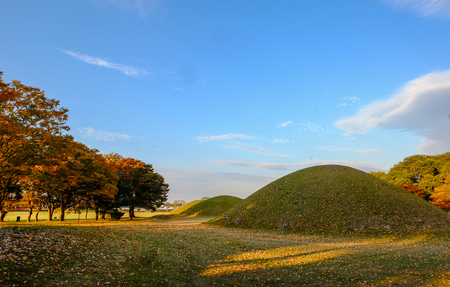 Tumuli royal tomb  in autumn foliage backgroung at sunset . Gyeongju, South Korea
