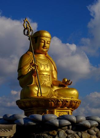 Golden Buddha statue at Haedong Yonggungsa Temple with blue sky and cloud in autumn , Busan, South Korea