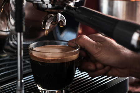 Close up of espresso pouring from coffee machine.Barista use professional coffee brewing.