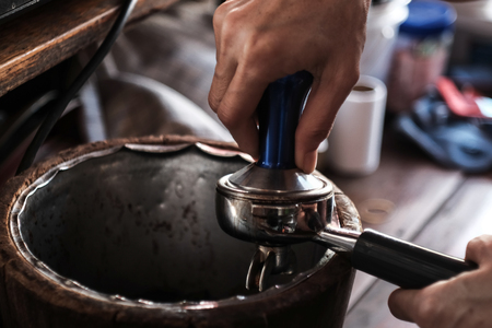Barista pressing ground coffee into portafilter by tamper to making coffee Фото со стока