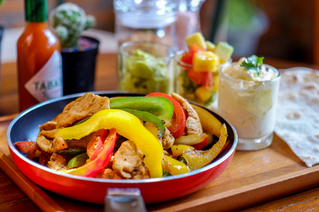 Mexican chicken fajitas in iron skillet with bell peppers and onion Фото со стока