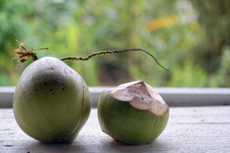 Fresh coconut on a wooden table and nature blur background