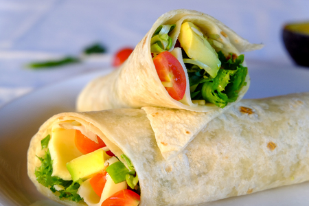 Vegeterian Burritos wraps with cheese and vegetables on white background. Beef burrito, mexican food. Фото со стока