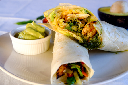 Burritos wraps with chicken , vegetables and  avocado sauce on white background. Chicken burrito, mexican food.