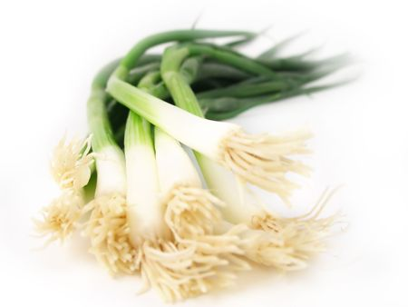lots of fresh spring onions on a white background