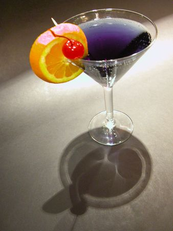 purple cocktail drink with slice of orange and a cherry