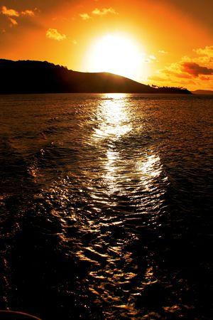 orange sun set over a silhuette of an island