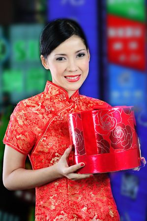 Young asian woman in a chinese dress receiving a gift Stock Photo - 6332617