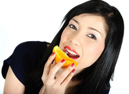 Beautiful young asian girl eating orange Stock Photo - 6332650