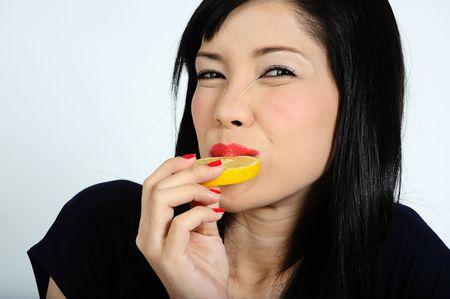 Beautiful young asian girl eating lemon Stock Photo - 6332677