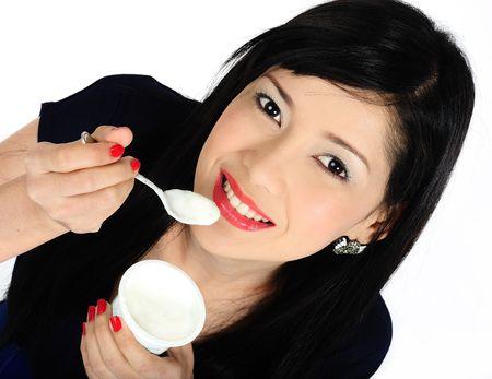 Beautiful young asian girl eating yogurt photo
