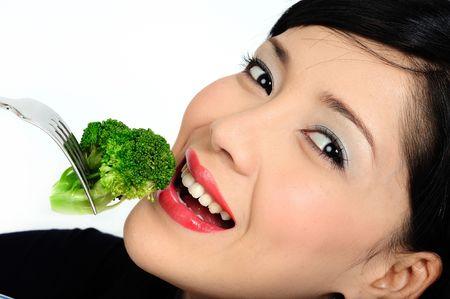 �broccoli: Hermosa joven asi�tica comer br�coli Foto de archivo