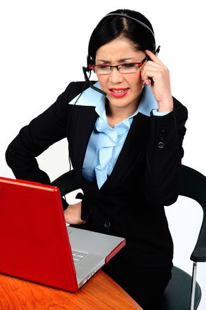 A businesswoman arguing with someone at the phone and looking at the computer photo