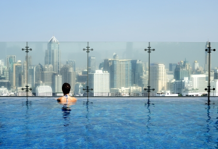swimming pool woman: Women in a swimming pool on the roof admiring a cityscape Stock Photo