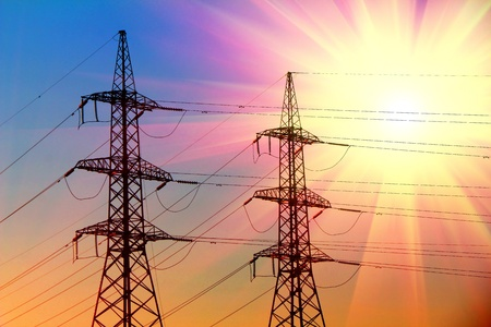 electric power transmission towers at sunset
