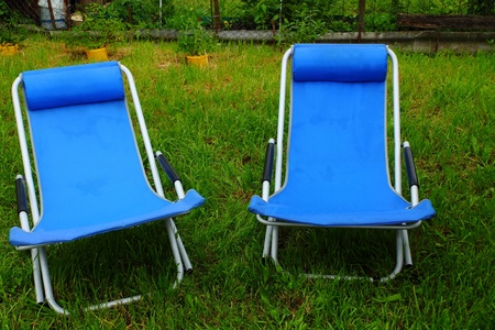 two folding deck chairs on the grass photo