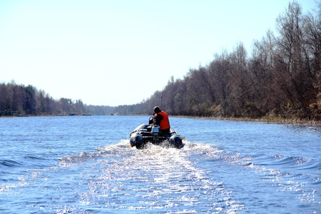 fisherman floating in an inflatable boat motor photo