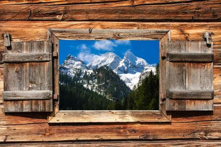Bekijk via een houten raam op een berglandschap met bos op de voorgrond Stockfoto
