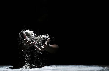 Chef hand clap and white flour on black background. Zdjęcie Seryjne
