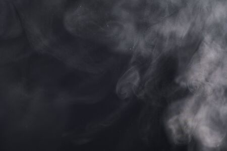 white smoke or steam on a black background.