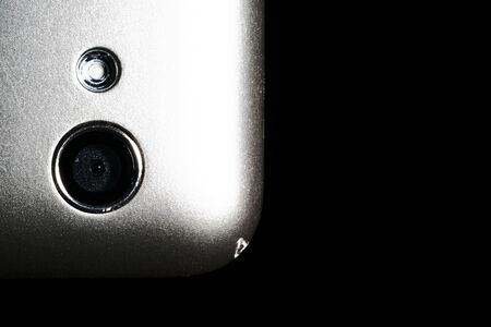 camera on a silver phone close-up on a black background.