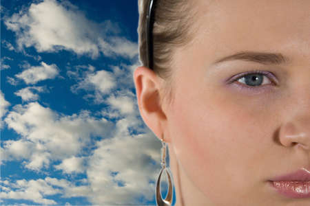 Portrait of the girl on a background of the sky with clouds photo